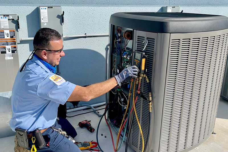 HVAC tech servicing AC system